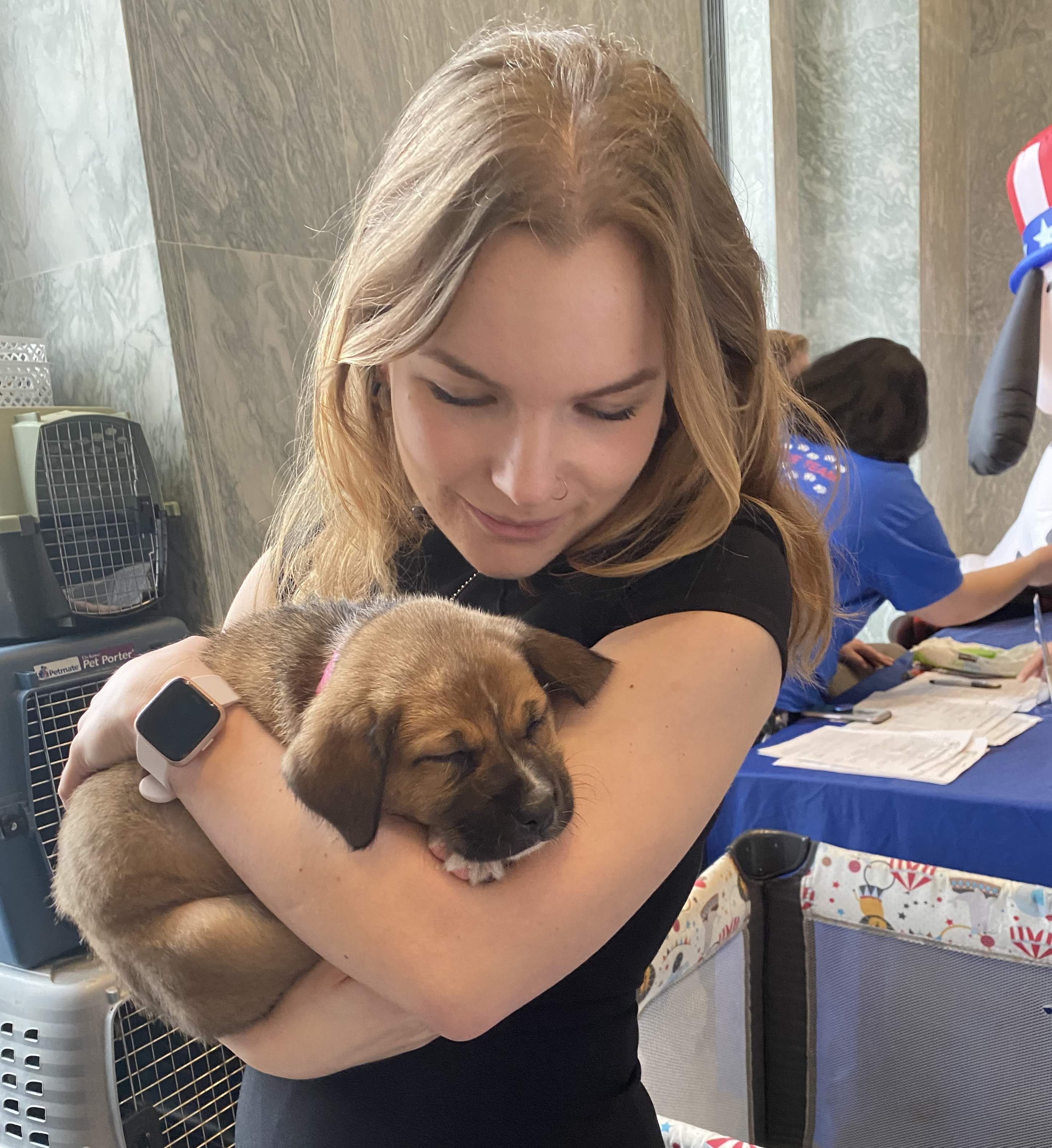 Elise with a puppy at the ASPCA Puppy Love Event